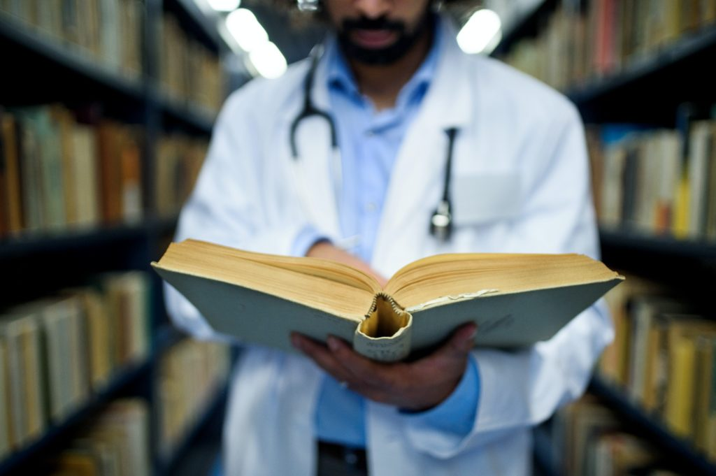 Unrecognizable doctor in library, studying information about corona virus